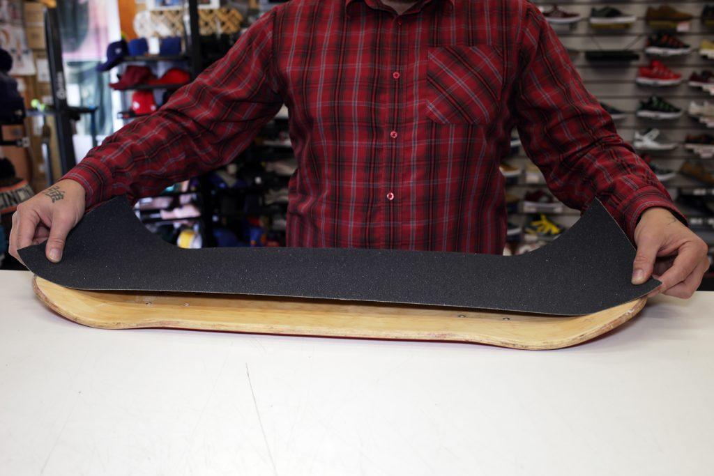 Man measuring out skateboard griptape